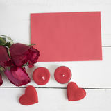 Rose , red heart shape, candles and red paper on white table. Stock Photo