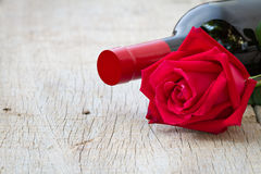 Rose with red wine bottle on wooden. Valentine's day, anniversar Stock Images