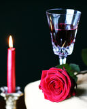 Rose red wine. Rose on gold table cloth with red wine in crystal glass and gold candle in background Royalty Free Stock Photo