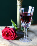 Rose red wine. Rose on gold table cloth with red wine in crystal glass and gold candlestick in background Stock Photography