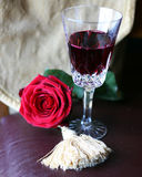 Rose and red wine. Rose on  table  with red wine in crystal glass Stock Photo
