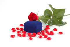Rose On A Ring Box. Rose resting on a velvet ring box with heart candies Royalty Free Stock Images