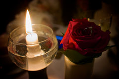Rose ring. Wedding wing next to a candel inside of a flower Royalty Free Stock Image