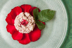 Rose risotto. Carnaroli rice rose risotto decorated with red rose petals and leaves, close up, on glass plate and green tablecloth Royalty Free Stock Photos