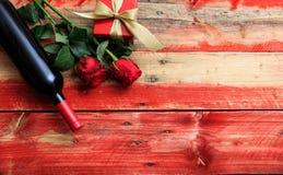 Rose roja Botella de vino rojo, rosas y un regalo en fondo de madera fotos de archivo libres de regalías
