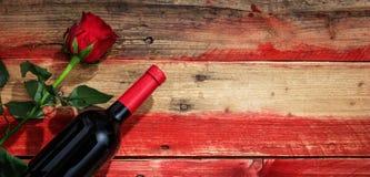 Rose roja Botella de vino rojo y rosa del rojo en fondo de madera imagenes de archivo