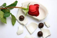Rose roja y chocolates que ponen en un cuenco quebrado Imágenes de archivo libres de regalías