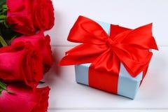 Rose rosa con un contenitore di regalo legato con un arco Modello per l'8 marzo, festa della Mamma, San Valentino Immagini Stock Libere da Diritti