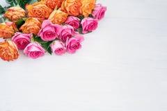 Rose rosa e gialle su fondo di legno bianco Copi lo spazio, a fotografia stock