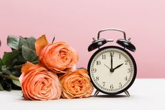 Rose roses and clock on pink background, daylight saving.  royalty free stock photo