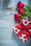Rose rosse aromatiche imballate del contenitore di regalo sulle celebrazioni del bordo di legno Fotografia Stock Libera da Diritti