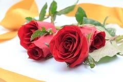 Rose rosse con il nastro dell'oro Fotografia Stock