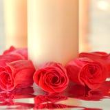 Rose rosse con la riflessione intorno ad una candela Fotografie Stock Libere da Diritti
