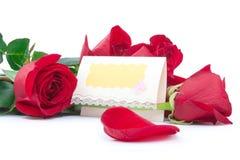 Rose rosse con una scheda in bianco del regalo Fotografie Stock Libere da Diritti