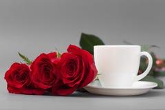 Rose rosse con una tazza di caffè di colore bianco su un fondo grigio Fotografie Stock Libere da Diritti