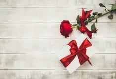 Rose rosse e contenitore di regalo su una tavola di legno Giorno felice dei biglietti di S immagini stock