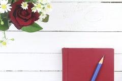 Rose rosse e diario rosso su fondo di legno bianco Fotografia Stock