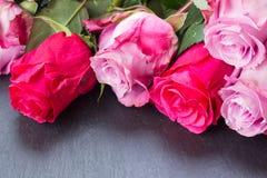 Rose rosse e rosa sulla tavola Immagini Stock Libere da Diritti