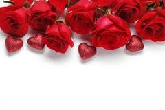 Rose rosse ed ornamenti di forma del cuore Immagini Stock