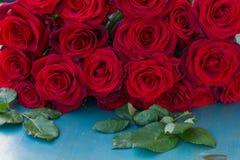 Rose rosse fresche sulla tavola blu Fotografia Stock Libera da Diritti
