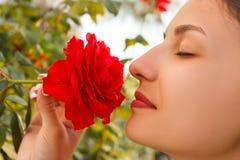 Rose rosse odoranti della giovane bella ragazza caucasica nel giardino il giorno soleggiato immagini stock libere da diritti