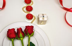 Rose rosse su un piatto bianco, sulle candele e sul giftbox Composizione romantica per il giorno del ` s del biglietto di S. Vale Immagine Stock Libera da Diritti