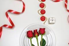 Rose rosse su un piatto bianco, sulle candele e sul giftbox Composizione romantica per il giorno del ` s del biglietto di S. Vale Fotografia Stock