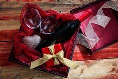 Rose rouge Bouteille de vin rouge, verres et un cadeau dans une boîte, fond en bois Photo libre de droits