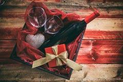 Rose rouge Bouteille de vin rouge, verres et un cadeau dans une boîte, fond en bois Photo stock