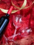 Rose rouge Bouteille et verres de vin rouge sur le textile rouge Photographie stock libre de droits