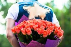 Rose rouge Homme se cachant derrière un bouquet des fleurs Photographie stock