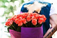 Rose rouge Homme se cachant derrière un bouquet des fleurs Photos libres de droits