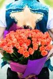 Rose rouge Homme se cachant derrière un bouquet des fleurs Photo stock