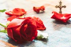 Rose rouge intelligente avec le fond d'un dieu de croix en métal de tache floue Photographie stock