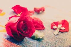 Rose rouge intelligente avec le fond d'un dieu de croix en métal de tache floue Photographie stock libre de droits