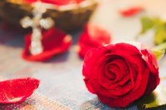 Rose rouge intelligente avec le fond d'un dieu de croix en métal de tache floue Image stock