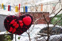 Rose rouge protections molles de coeurs accrochant sur une corde Photos stock
