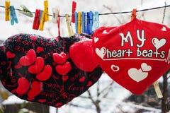 Rose rouge protections molles de coeurs accrochant sur une corde Image stock