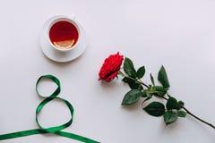 Rose rouge sur un fond blanc, ruban avant le 8 mars image stock