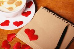 Rose rouge Tasse de cappuccino avec un art de latte sous forme de coeurs, de vieux carnet de papier et de stylo sur une table en  photos stock