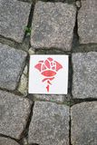 Rose route in Hildesheim Germany. Paving stones with ceramic plaques with rose symbol marking self-guided sightseeing tour Royalty Free Stock Photo