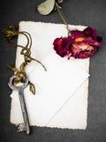 Rose sèche de rouge, clé rouillée et photographie vide, Photographie stock