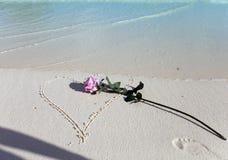 Rose se trouve sur le sable au coeur tiré et une ombre de la main qui l'a jetée Photographie stock