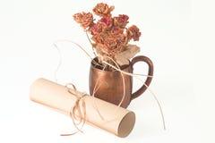 Rose secche nella tazza e nel rotolo del metallo Fotografie Stock Libere da Diritti