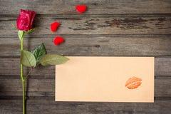 Rose simple de rouge avec l'enveloppe avec le baiser et les petits coeurs, sur le bro Photos libres de droits
