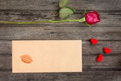 Rose simple de rouge avec l'enveloppe avec le baiser et les petits coeurs, sur le bro Photographie stock