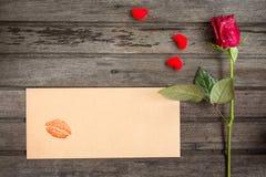 Rose simple de rouge avec l'enveloppe avec le baiser et les petits coeurs, sur le bro Images libres de droits