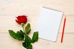 Rose simple de rouge avec le bloc-notes clair sur la table Image stock