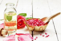 Rose spa bath salt and massage oil. Bath salt in a bowl and bottle of massage oil arranged with rose and petals royalty free stock photos