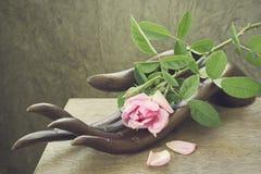 Rose stellte auf hölzerne Skulptur ein Lizenzfreies Stockbild